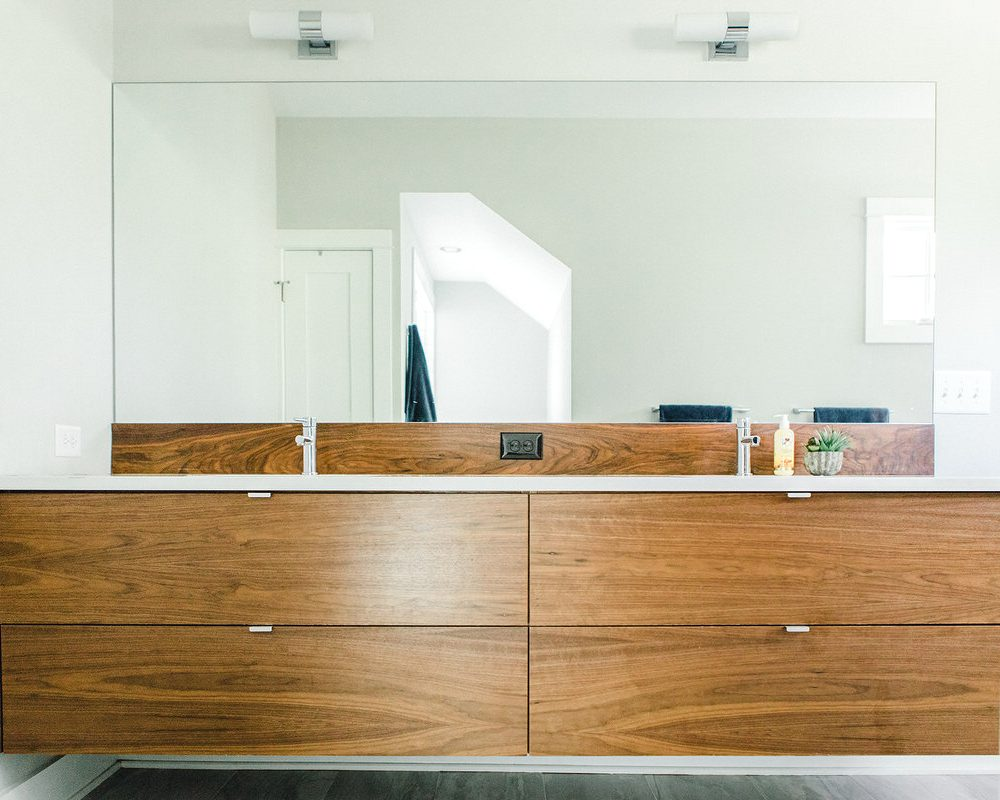 This custom floating walnut vanity in the master bathroom features chrome faucets on white quartz countertops.